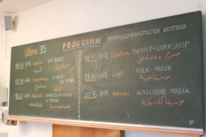 Programm des Festes auf deutsch und arabisch auf der Tafel im Hörsaal